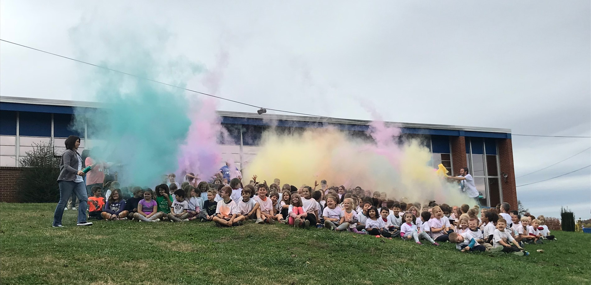 Students sitting on hill after color run