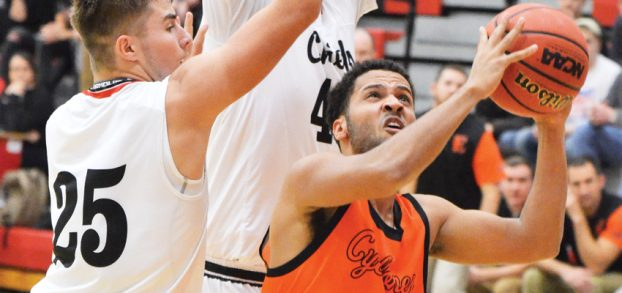 Star Photo/Ivan Sanders Christian Price works hard for a lay up against a pair of Cherokee defenders.